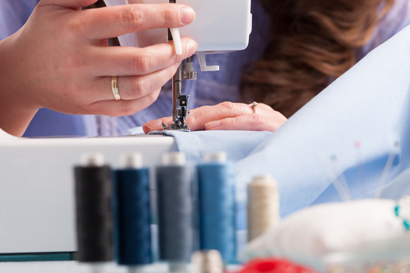 Hands on sewing machine with reels of colour threads and sewing
